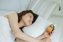 目覚まし時計を見る日本人女性