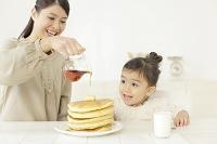 パンケーキにシロップをかける母と見つめる娘