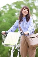 緑の中で自転車を押す日本人女性