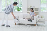 掃除機をかける男性とソファに座って両足を上げる日本人女性