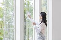窓を掃除する日本人女性
