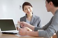 ノートパソコンを見せて説明をする日本人ビジネスウーマン