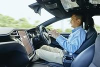 笑顔で自動運転車を運転する日本人男性