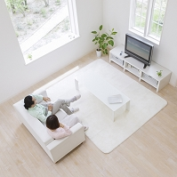 ソファに座りテレビを見る中高年夫婦