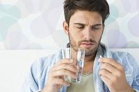 薬を飲む外国人男性
