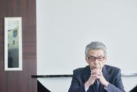深刻な表情のシニアの日本人ビジネスマン