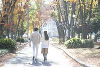 晩秋の並木道を散歩するカップル