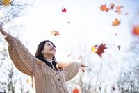 紅葉の中で手を広げる日本人女性