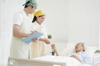 介護ベッドの介護老人に体温計を渡す介護士