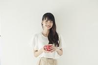 カップを持って見つめる日本人女性