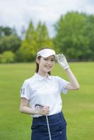 ゴルフクラブを持つ若い日本人女性