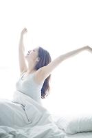 ベッドの上で手を伸ばす日本人女性