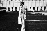 細い柱の上を歩くコートの女性