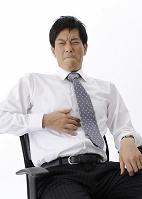 胃を押さえ顔をしかめるビジネスマン