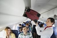 スーツケースを荷物入れに入れるフライトアテンダント