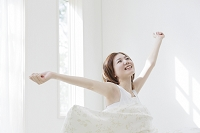 ベッドで背伸びをする日本人女性