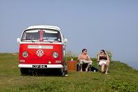 フォルクスワーゲンバスとキャンプする外国人カップル