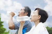 ペットボトルの水を飲むシニア