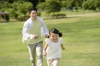 新緑の公園で駆けっこする日本人親子