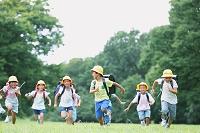 草原で走る日本人の小学生たち