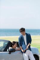 オープンカーに座ってiPadを見ているカップル