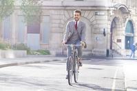 自転車に乗るスーツの男性