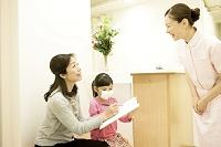 待合室で待つ親子(マスクの子供) 問診票を書く1
