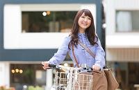自転車を押して街を歩く日本人女性