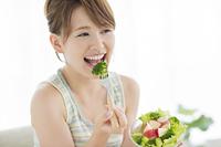 野菜サラダを食べる日本人の若い女性