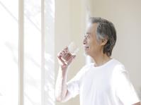 窓辺で水を飲むシニアの日本人男性