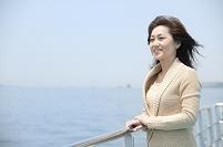 フェリーのデッキで海を見る中年日本人女性