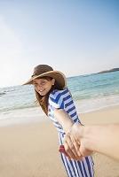 手を繋いで砂浜を歩く日本人女性