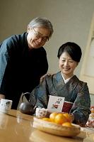お正月に着物で年賀状を読むシニア夫婦