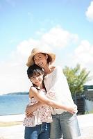 海辺に立つ笑顔の日本人親子