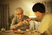 日本酒で晩酌をする親子