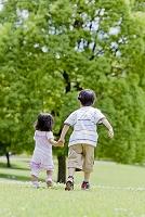 公園を走る兄と妹の後ろ姿