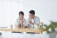 スマートフォンを見てガッツポーズをする日本人夫婦