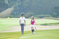 ゴルフ場で歩くカップル