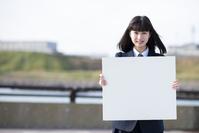 ホワイトボードを持つ女子学生