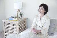 ベッドで微笑むミドル日本人女性
