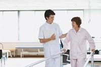 リハビリ施設にいる笑顔のシニア女性と若い男性看護師
