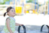 ベンチに座り笑っている日本人の女の子