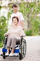 車イスを押す日本人女性介護士