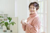 マグカップを持って振り返るシニア日本人女性