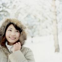 雪の林でフードを被る日本人女性