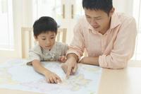 テーブルで地図を広げるお父さんと子供