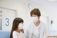 病院の待合室でマスク姿のシニア女性と孫