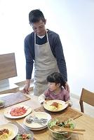 父親を手伝ってパスタ皿を運ぶ幼い女の子