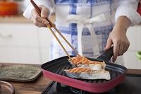 塩鮭をグリルパンで焼く女性