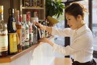 お酒のビンを持つエプロン姿の日本人女性
